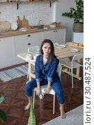 Купить «Beautiful woman in denim overalls sits on a chair in the kitchen.», фото № 30487524, снято 18 марта 2019 г. (c) Женя Канашкин / Фотобанк Лори