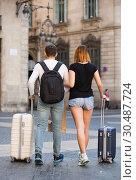 Купить «Young man and woman walking with baggage», фото № 30487724, снято 25 мая 2017 г. (c) Яков Филимонов / Фотобанк Лори