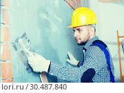 Купить «Smiling builder in the helmet is plastering the wall», фото № 30487840, снято 3 июня 2017 г. (c) Яков Филимонов / Фотобанк Лори