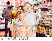 Купить «Two small nice sisters holding bottled water», фото № 30487868, снято 20 января 2018 г. (c) Яков Филимонов / Фотобанк Лори