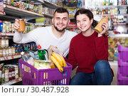 Купить «vigorous young family choosing purchasing canned food for week at supermarket», фото № 30487928, снято 14 марта 2017 г. (c) Яков Филимонов / Фотобанк Лори