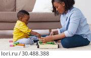 Купить «mother and baby playing with toy blocks at home», видеоролик № 30488388, снято 24 марта 2019 г. (c) Syda Productions / Фотобанк Лори