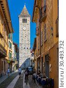 Купить «View of clock tower on Via Umberto l, cobbled street in Cannobio, Lake Maggiore, Piedmont, Italy, Europe», фото № 30493732, снято 12 сентября 2018 г. (c) age Fotostock / Фотобанк Лори
