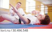 Martial arts. Two athletic men training their aikido skills in the studio. Lying on the floor. Стоковое видео, видеограф Константин Шишкин / Фотобанк Лори