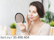 Portrait Of Beautiful Young Woman with Natural Makeup applying white Under Eye Patches Beauty Mask On Face. Girl with eye patches. Woman with collagen pads under her eyes. Стоковое фото, фотограф Сергей Тимофеев / Фотобанк Лори