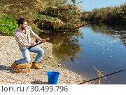 Купить «Adult man standing near river and pulling fish expressing emotions of dedication», фото № 30499796, снято 15 марта 2019 г. (c) Яков Филимонов / Фотобанк Лори