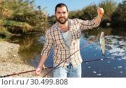 Купить «Happy fisherman pulls fish out of the river», фото № 30499808, снято 15 марта 2019 г. (c) Яков Филимонов / Фотобанк Лори