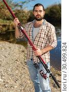 Купить «Adult man standing outdoors with angling rod planning to fishing», фото № 30499824, снято 15 марта 2019 г. (c) Яков Филимонов / Фотобанк Лори