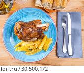Купить «Close up of delicious baked pork knuckle with potatoes, served», фото № 30500172, снято 19 апреля 2019 г. (c) Яков Филимонов / Фотобанк Лори