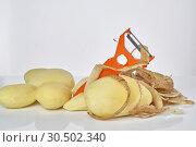 Peeled raw potatoes, peeling potatoes and a peeler on a white background close-up. Стоковое фото, фотограф Андрей Зарин / Фотобанк Лори