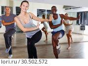 Купить «Cheerful people practicing vigorous lindy hop movements in dance class», фото № 30502572, снято 30 июля 2018 г. (c) Яков Филимонов / Фотобанк Лори