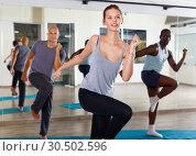 Купить «Cheerful people practicing vigorous lindy hop movements in dance class», фото № 30502596, снято 30 июля 2018 г. (c) Яков Филимонов / Фотобанк Лори
