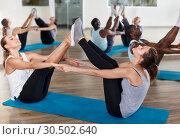 Купить «People doing stretching exercises in pairs», фото № 30502640, снято 30 июля 2018 г. (c) Яков Филимонов / Фотобанк Лори
