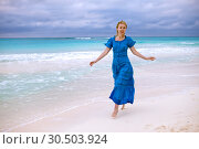 Купить «The woman in a long blue dress goes on the sea coast Cayo Largo island, Cuba», фото № 30503924, снято 1 февраля 2013 г. (c) Куликов Константин / Фотобанк Лори