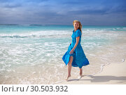 Купить «The woman in a long blue dress goes on the sea coast Cayo Largo island, Cuba», фото № 30503932, снято 1 февраля 2013 г. (c) Куликов Константин / Фотобанк Лори