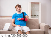 Купить «Young man with injured arm sitting on the sofa», фото № 30505080, снято 19 сентября 2018 г. (c) Elnur / Фотобанк Лори