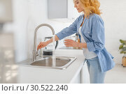 Купить «Young woman with glass at the sink on the kitchen», фото № 30522240, снято 23 февраля 2019 г. (c) Tryapitsyn Sergiy / Фотобанк Лори