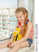 Купить «Russia, Samara, March 2017: A little girl is sitting with a plush dog on the windowsill of a high-rise building. Danger.», фото № 30522656, снято 14 марта 2017 г. (c) Акиньшин Владимир / Фотобанк Лори