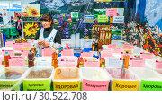 Купить «Russia, Samara, March 2017: A woman sells Siberian honey at a fair. Text in Russian: good health linseed oil immunity», фото № 30522708, снято 19 марта 2017 г. (c) Акиньшин Владимир / Фотобанк Лори