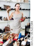 Купить «woman selecting sandals in footgear center», фото № 30523584, снято 26 сентября 2016 г. (c) Яков Филимонов / Фотобанк Лори