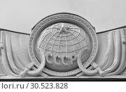 Купить «Медальон с изображением земного шара в окружении знамен на фасаде Театра сказки (павильон номер 9) на ВДНХ в Москве», фото № 30523828, снято 5 апреля 2019 г. (c) Наталья Николаева / Фотобанк Лори