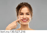 Купить «beautiful young woman pointing to her nose», фото № 30527216, снято 20 января 2019 г. (c) Syda Productions / Фотобанк Лори