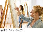 Купить «woman with easel drawing at art school studio», фото № 30527396, снято 26 мая 2017 г. (c) Syda Productions / Фотобанк Лори