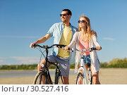Купить «happy young couple riding bicycles at seaside», фото № 30527416, снято 23 июля 2017 г. (c) Syda Productions / Фотобанк Лори