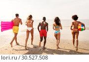 Купить «friends run with beach ball and swimming mattress», фото № 30527508, снято 29 июля 2018 г. (c) Syda Productions / Фотобанк Лори