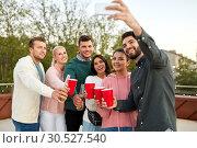 Купить «friends with drinks taking selfie at rooftop party», фото № 30527540, снято 2 сентября 2018 г. (c) Syda Productions / Фотобанк Лори