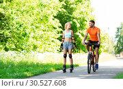 Купить «happy couple with rollerblades and bicycle riding», фото № 30527608, снято 5 июля 2015 г. (c) Syda Productions / Фотобанк Лори
