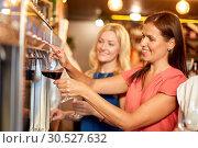 Купить «happy women pouring wine from dispenser at bar», фото № 30527632, снято 25 июня 2018 г. (c) Syda Productions / Фотобанк Лори