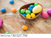 Купить «chocolate easter egg and candy drops on table», фото № 30527756, снято 15 марта 2018 г. (c) Syda Productions / Фотобанк Лори