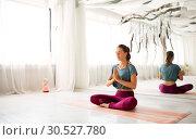 Купить «woman meditating in lotus pose at yoga studio», фото № 30527780, снято 21 июня 2018 г. (c) Syda Productions / Фотобанк Лори