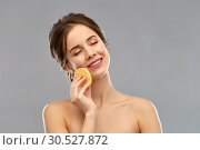 Купить «young woman cleaning face with exfoliating sponge», фото № 30527872, снято 20 января 2019 г. (c) Syda Productions / Фотобанк Лори
