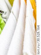 Купить «White and colored linen and towels to be dried on the clothesline», фото № 30528164, снято 2 октября 2018 г. (c) Tetiana Chugunova / Фотобанк Лори