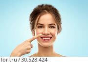 Купить «beautiful young woman pointing to her nose», фото № 30528424, снято 20 января 2019 г. (c) Syda Productions / Фотобанк Лори