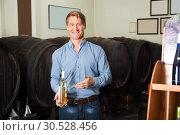 Купить «customer picking bottle in wine store», фото № 30528456, снято 25 мая 2019 г. (c) Яков Филимонов / Фотобанк Лори
