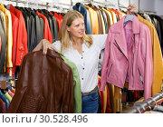 Купить «Attractive young woman choosing stylish leather jacket in store», фото № 30528496, снято 5 сентября 2018 г. (c) Яков Филимонов / Фотобанк Лори