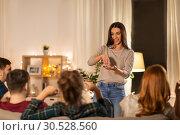 Купить «happy friends playing charades at home in evening», фото № 30528560, снято 22 декабря 2018 г. (c) Syda Productions / Фотобанк Лори
