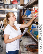 Купить «Woman customer holding shop list and looking tools at shelves in store», фото № 30528652, снято 20 сентября 2018 г. (c) Яков Филимонов / Фотобанк Лори