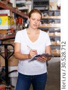Купить «Young woman standing near racks in build store bebore buying tools», фото № 30528712, снято 20 сентября 2018 г. (c) Яков Филимонов / Фотобанк Лори