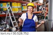 Купить «Female in uniform and helmet holding saw and standing near racks in build store», фото № 30528752, снято 20 сентября 2018 г. (c) Яков Филимонов / Фотобанк Лори