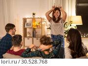 Купить «happy friends playing charades at home in evening», фото № 30528768, снято 22 декабря 2018 г. (c) Syda Productions / Фотобанк Лори
