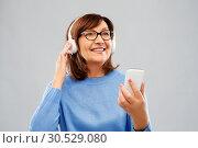 Купить «senior woman in headphones listening music on cell», фото № 30529080, снято 8 февраля 2019 г. (c) Syda Productions / Фотобанк Лори