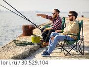 Купить «happy friends with fishing rods on pier», фото № 30529104, снято 8 сентября 2018 г. (c) Syda Productions / Фотобанк Лори