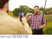 Купить «friend photographing fisherman with fish at lake», фото № 30529116, снято 8 сентября 2018 г. (c) Syda Productions / Фотобанк Лори
