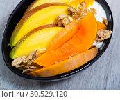 Купить «Sweet pumpkin and mango and whipped cream with oat-flakes at plate», фото № 30529120, снято 26 апреля 2019 г. (c) Яков Филимонов / Фотобанк Лори