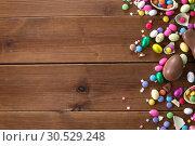 Купить «chocolate eggs and candy drops on wooden table», фото № 30529248, снято 22 марта 2018 г. (c) Syda Productions / Фотобанк Лори