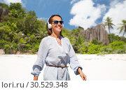 Купить «woman with headphones walking along summer beach», фото № 30529348, снято 15 июня 2018 г. (c) Syda Productions / Фотобанк Лори